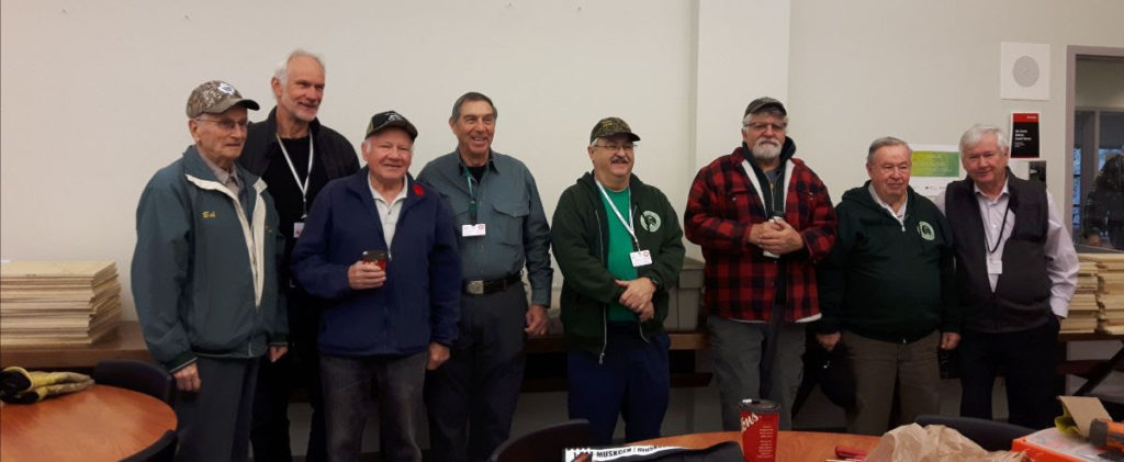 A group of the Parry Sound Anglers & Hunters stands with the bat house building kits they made for the All About Bats event hosted with GBBR.